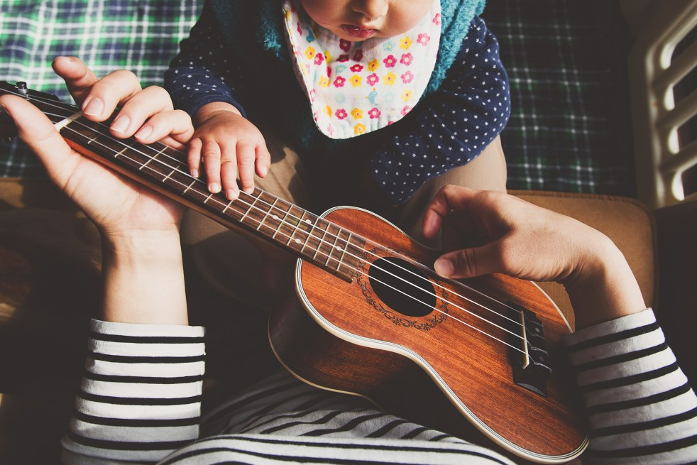 Baby playing with a ukulele with parent