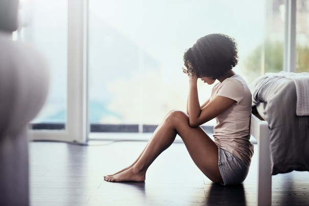 Young woman suffering from depression sitting on floor covering her face.