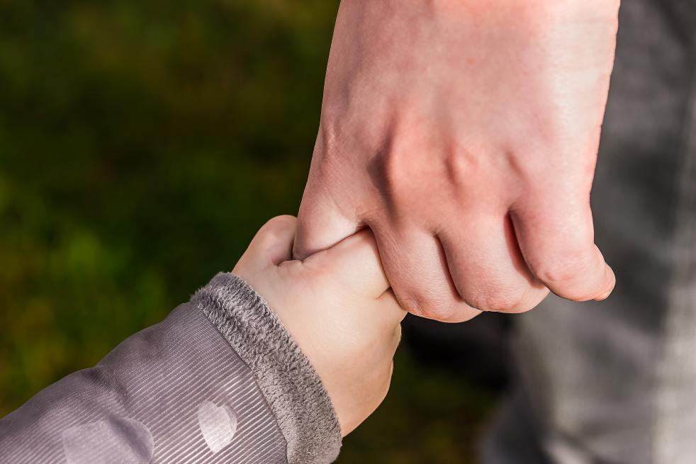 Close-up of child holding parent's hand
