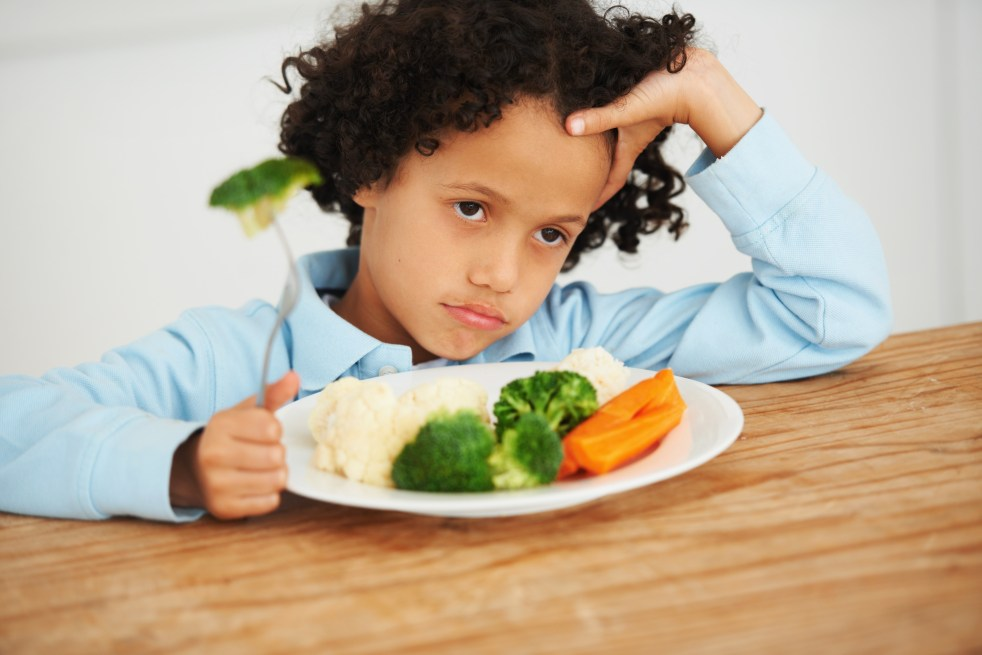 An unimpressed-looking little boy sitting in front of a plate of vegetables