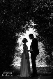 bride and groom under tree arch