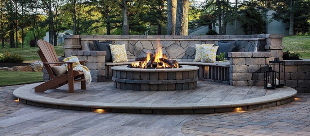Outdoor raised pit fireplace with seating around it.
