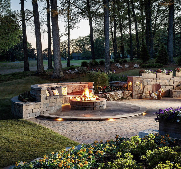 Patio with a fireplace and concrete seating.