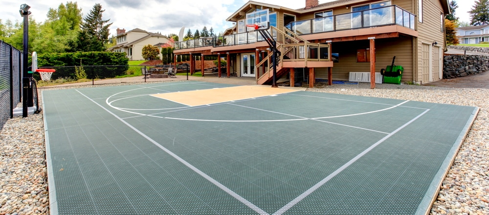 Multi-sport court with an inground basketball net in the backyard of an Ottawa home.