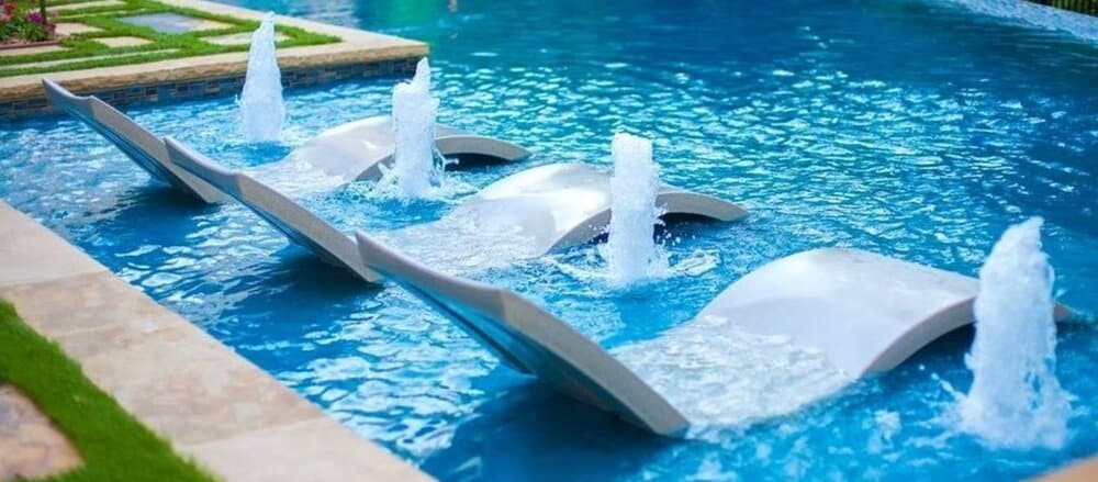 Three in-pool loungers with four water features beside them.