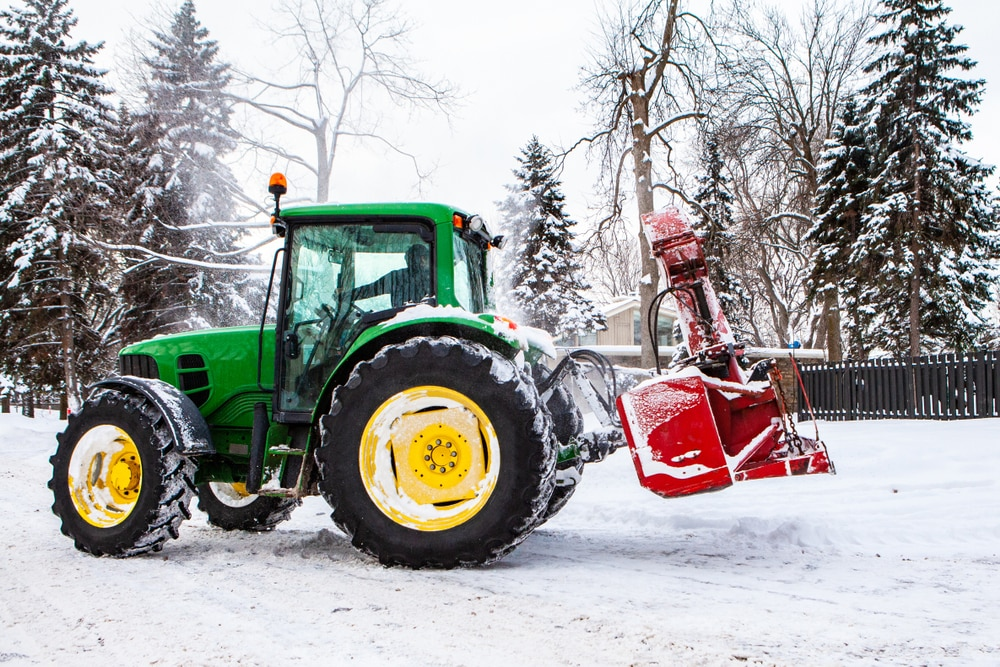 Tractor with snow blower attachment blowing snow from a residential driveway.