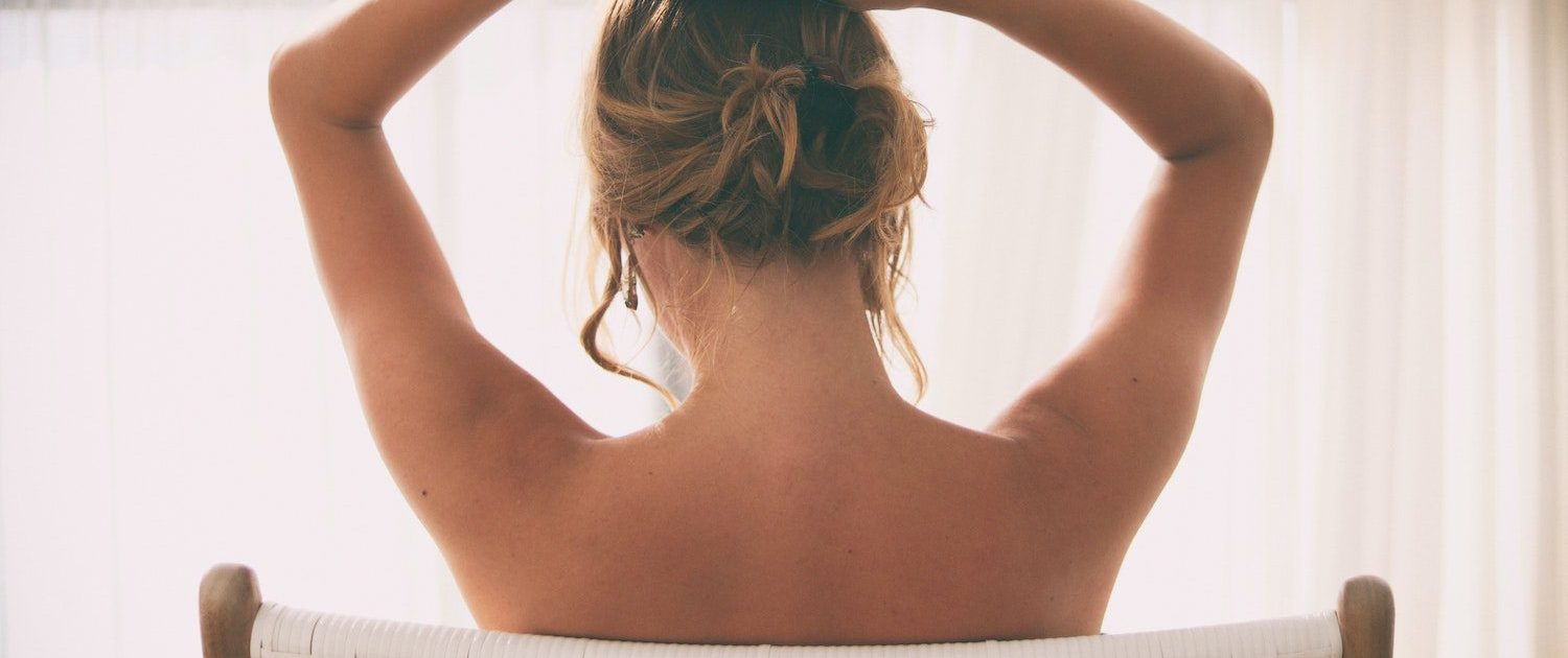 naked woman sitting showing off arm liposuction results