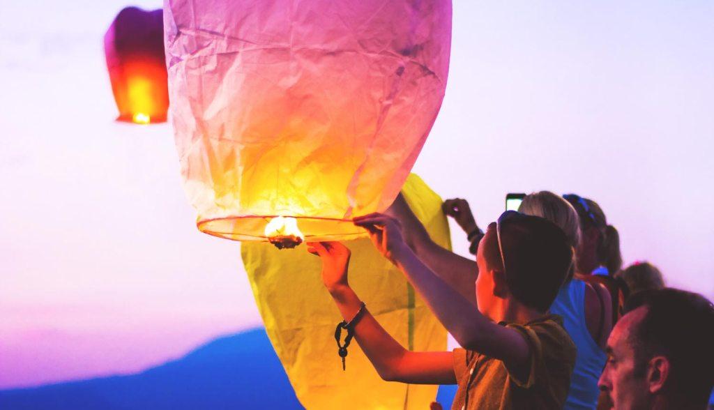 A group lighting a lantern, floating lanterns Myanmar