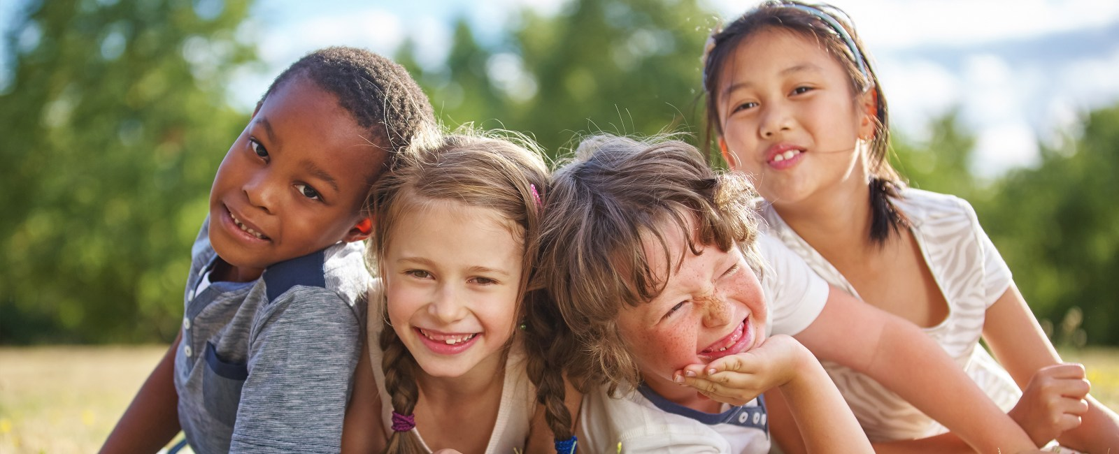 Four diverse kids gather close and smile