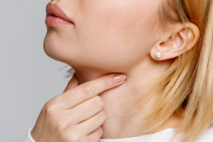 Close up of woman touching throat indicting sore throat