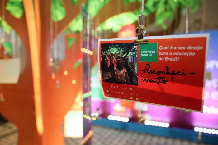 """Photo of a card written """"Acknowledgment"""" hanging from a scenic tree."""