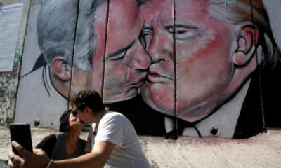 Donald Trump and Benjamin Netanyahu share a kiss on a wall mural in Bethlehem