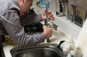 A plumber fixes a tap in the kitchen.