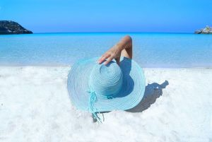 Girl with a blue hat on a beach who thought moving to a warmer climate was a good idea