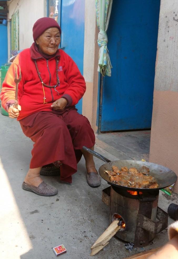 Grand-mère cuisine au feu de bois