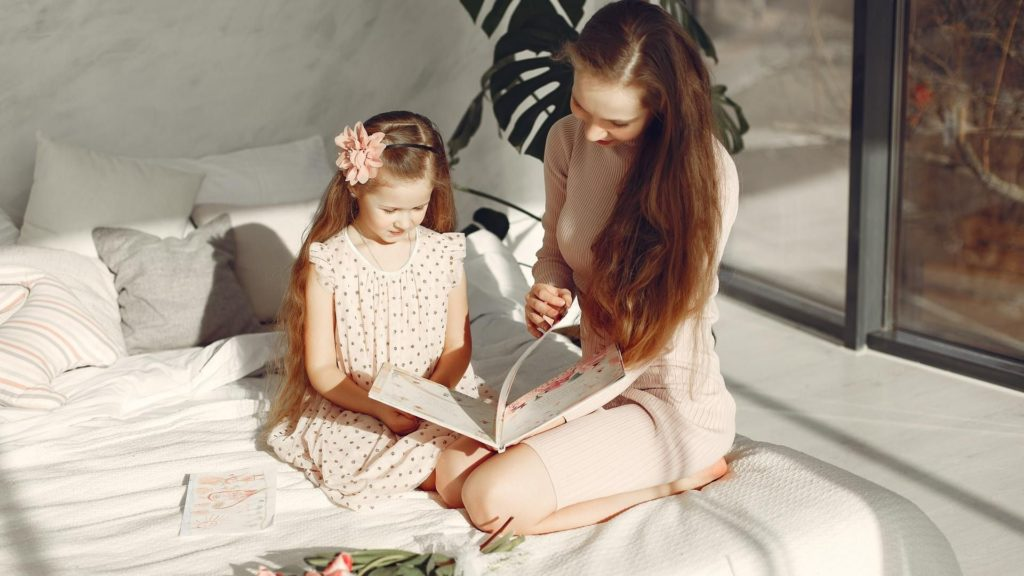 picture of mom and daughter reading book on bed