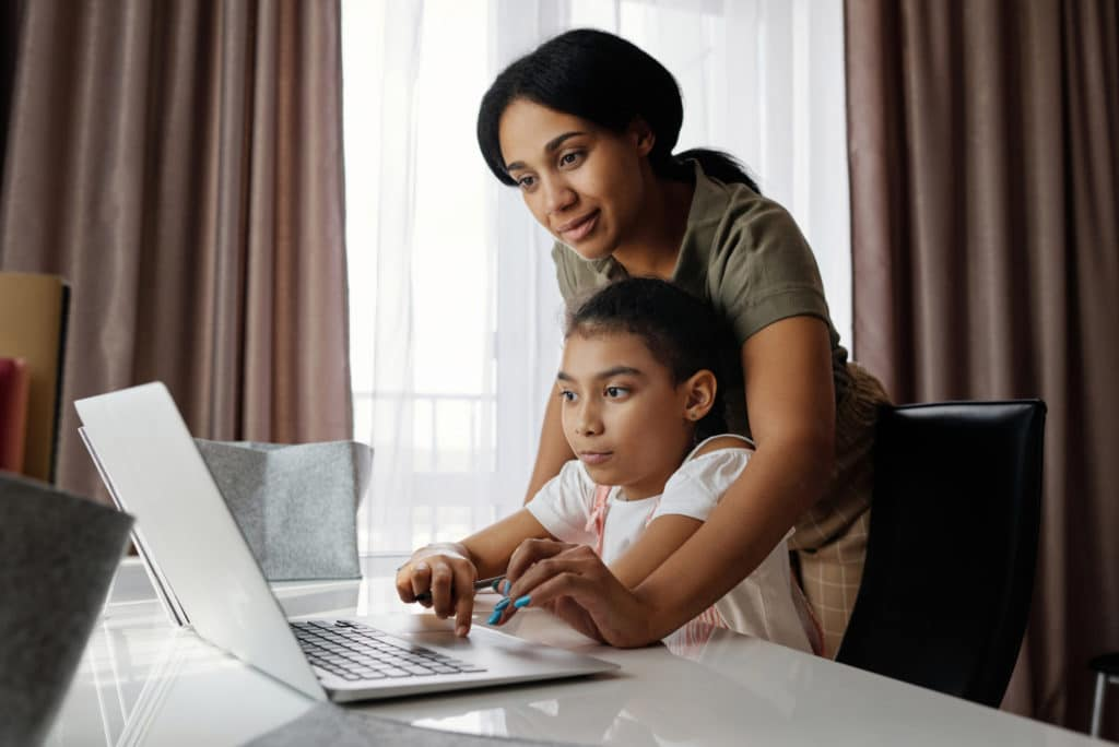 picture of mother helping student on computer
