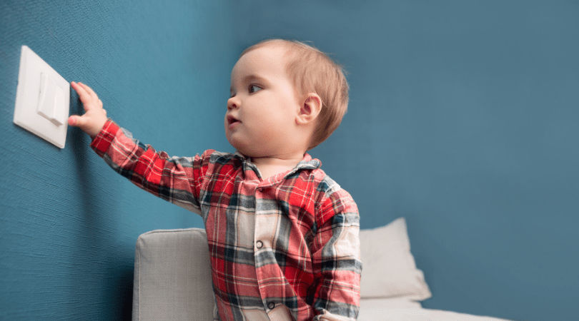 a baby touches a dirty light switch and helps with germ spreading