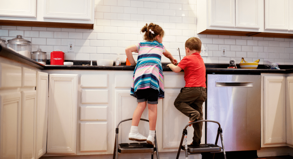 two children learn the life skill of doing dishes