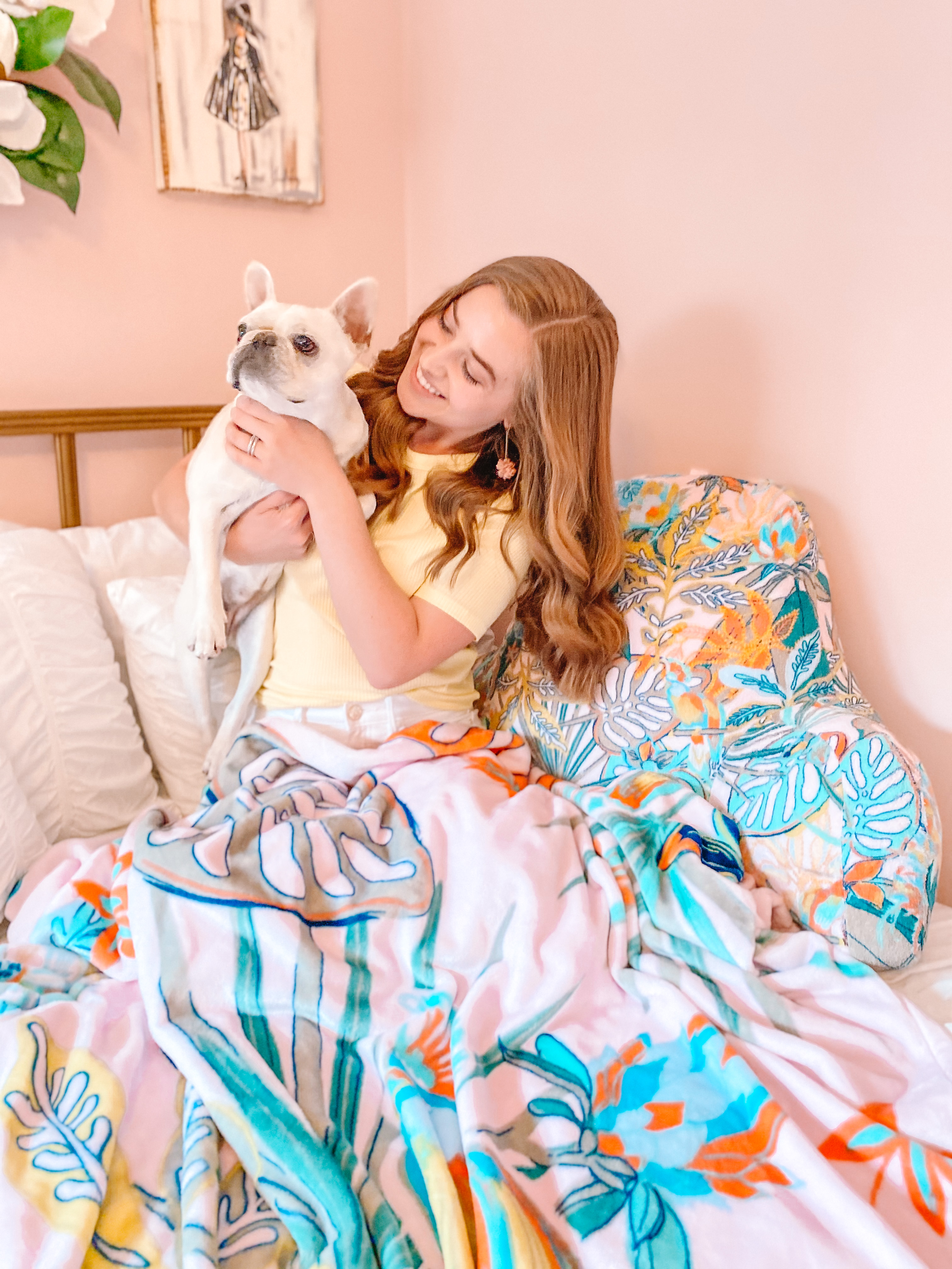 woman hold french bulldog puppy in bedroom. she has a vera bradley blanket and matching buddy pillow in the pattern rain forest canopy