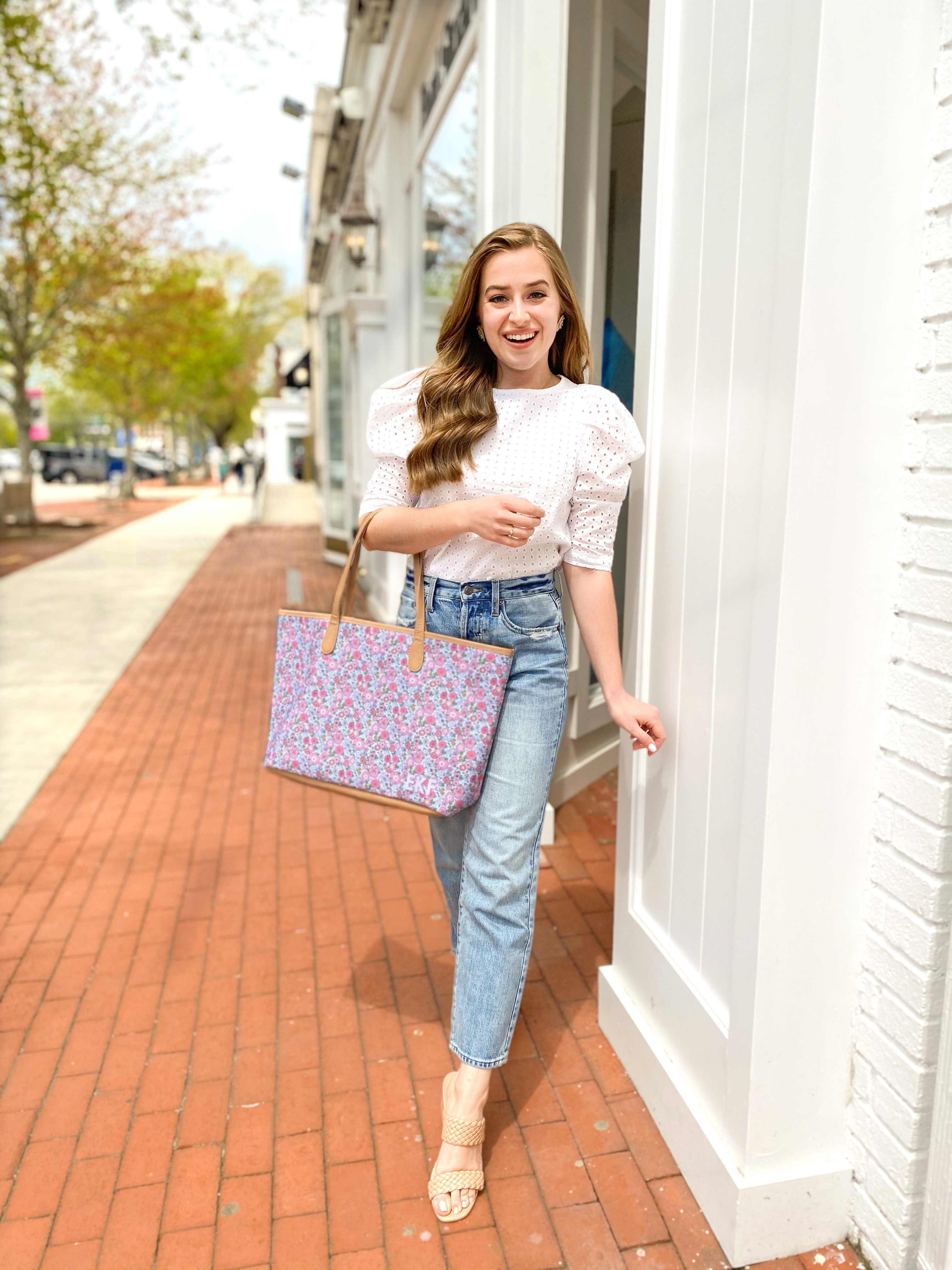 girl walks in southampton with mom jeans, a white eyelet blouse and a floral barrington tote