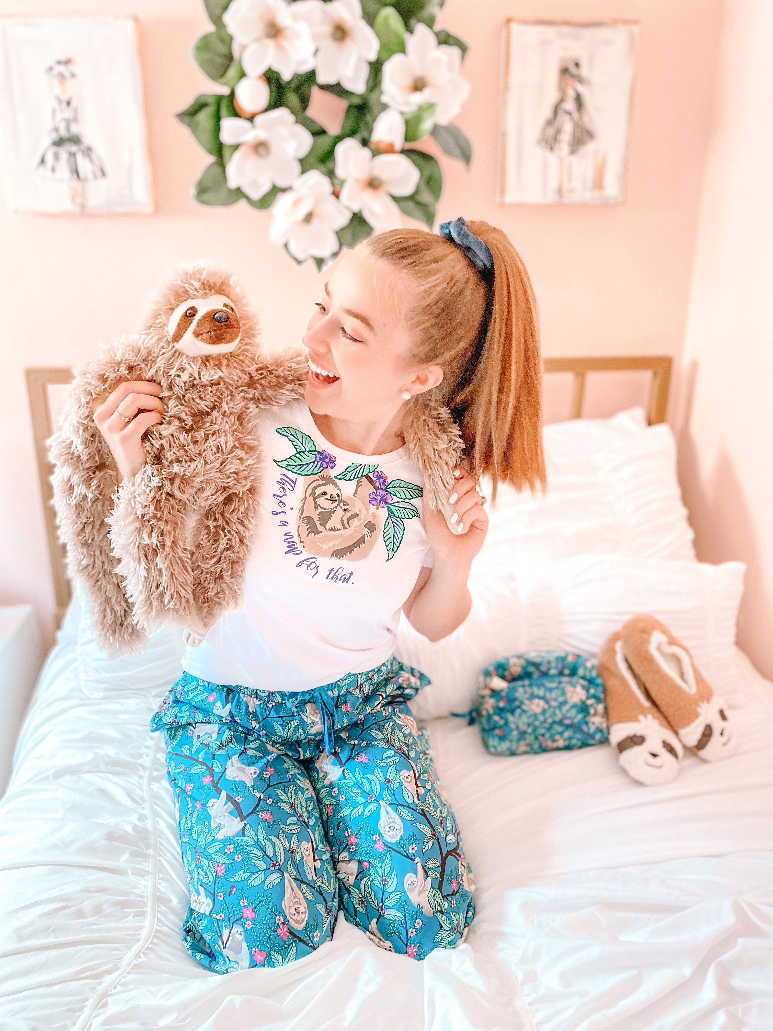 girl smiles with sloth toy in vera bradley sloth hanging around pajams in pink bedroom with white bedding