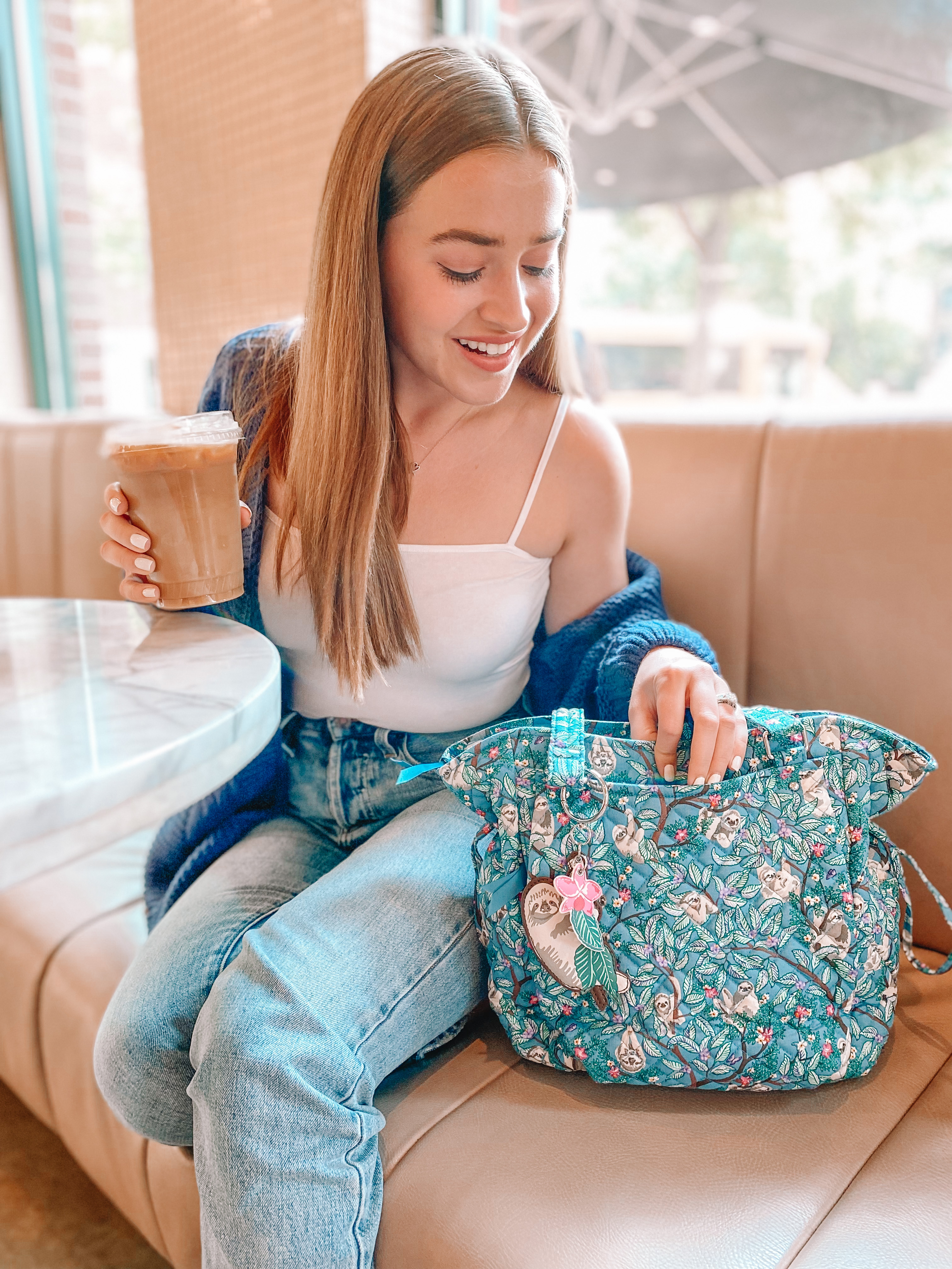 girl looks in sloth purse in coffee shop