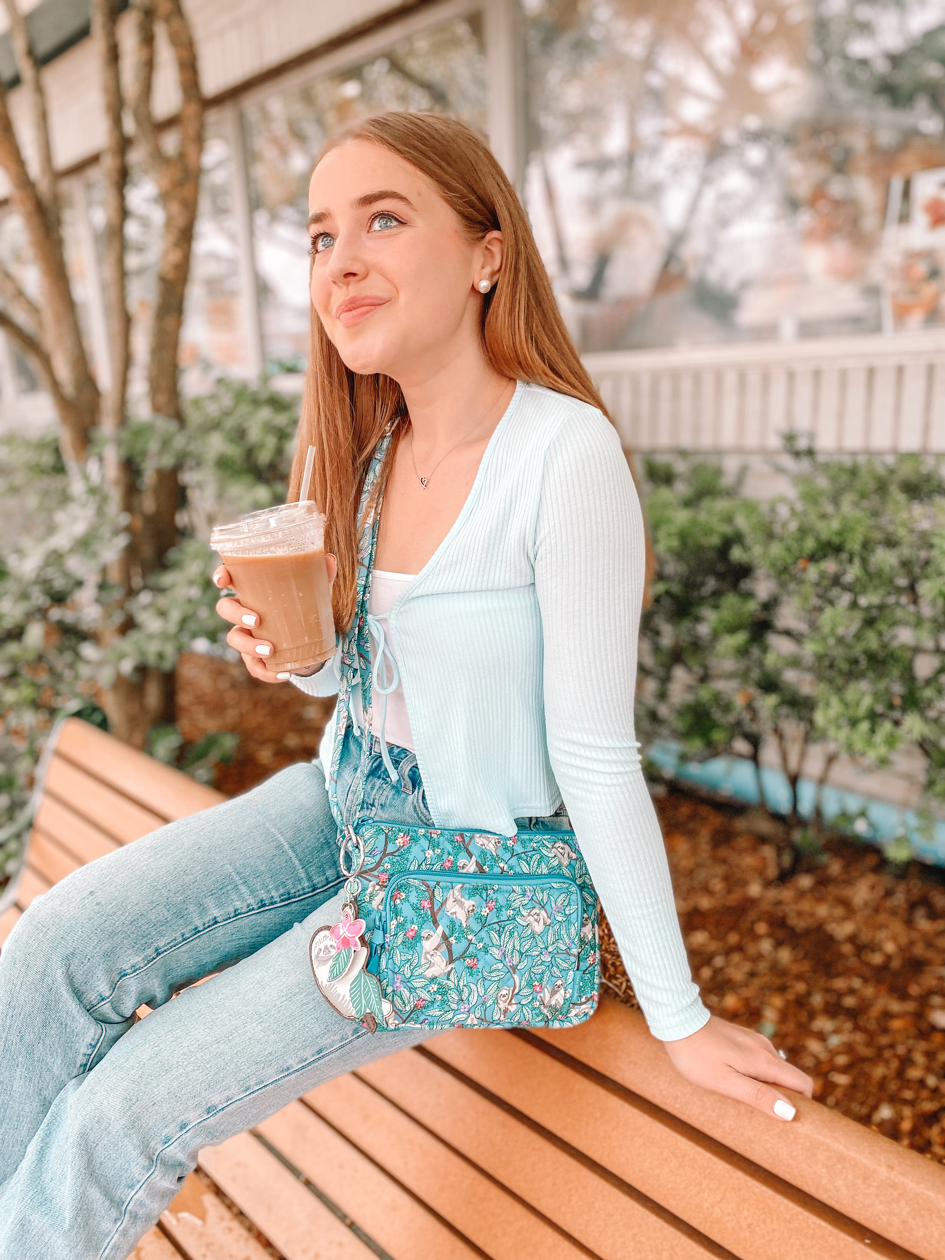 girl smiles softly with hanging around bag from vera bradley and iced coffee