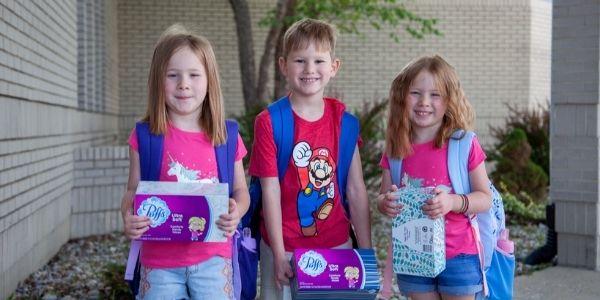 Three kids posing for camera on first day of school