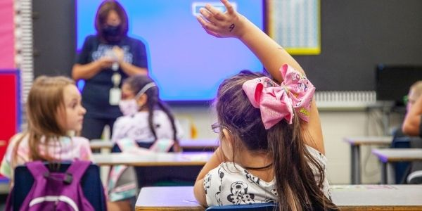 Student with hand raised in class