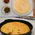 Cheesy jalapeño bacon cornbread in cast iron skillet batter in bowl
