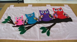 A  vibrant and colorful group of Appliqued owls for a wall hanging