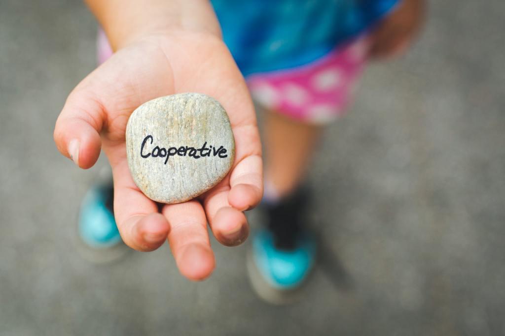"""Mano de niña que sujeta una piedra con el texto """"Cooperative"""". Para influir con el storytelling hay que llevar las historias con cuidado."""