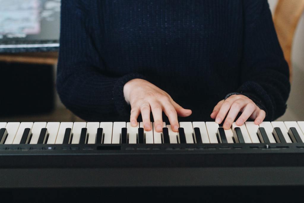 Hombre tocando un teclado de piano.