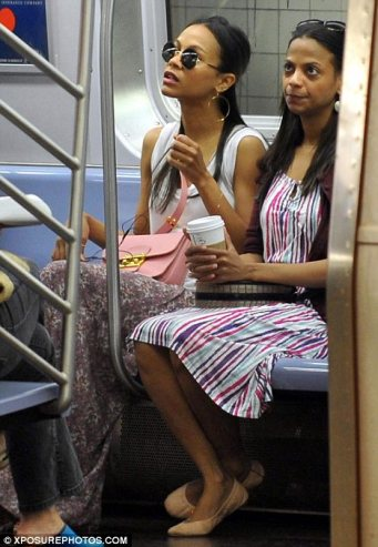 Zoe Saldana wearing round sunglasses on the subway with sister