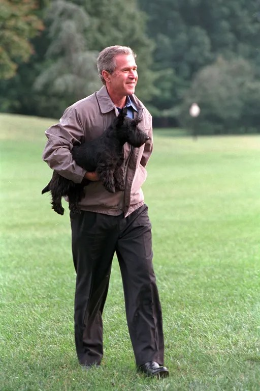 President George W. Bush carries Barney after disembarking Marine One, Sept. 3, 2001. Courtesy of the George W. Bush Presidential Library.