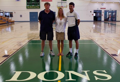 Jeff King, Kira Fay, and Greg Tebbe stand on the newly renovated floor in JR Richards Gymnasium at Santa Barbara High School.