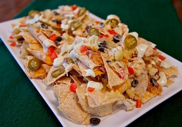Hot cauliflower nachos served with a garlic avocado crema ready to be devoured.