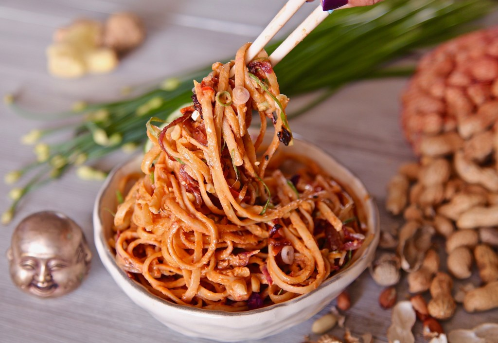 Spicy Noodles In Peanut Sauce pulled up by chopsticks