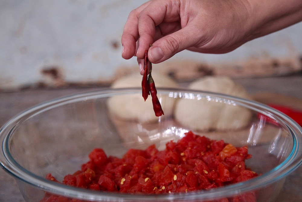 Adding Chile de arbol to crushed tomatoes and Clamato. I was able to buy all my ingredients at Walmart!