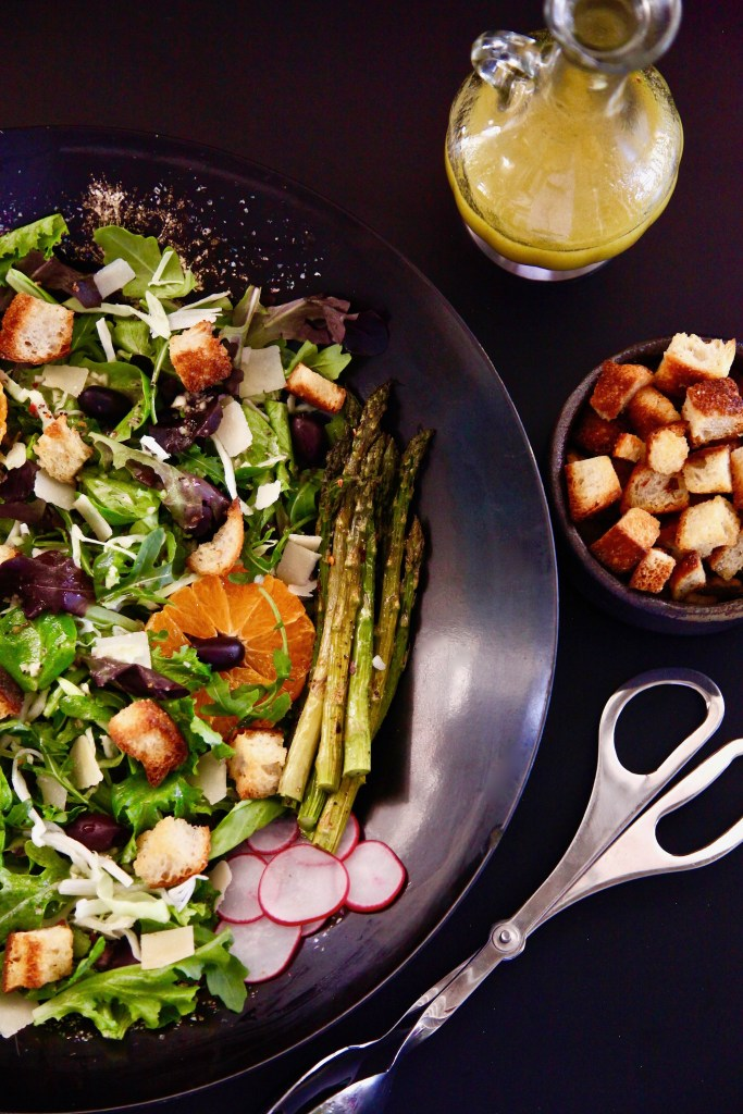Roasted Asparagus Spring Salad with a side of croutons and salad dressing.