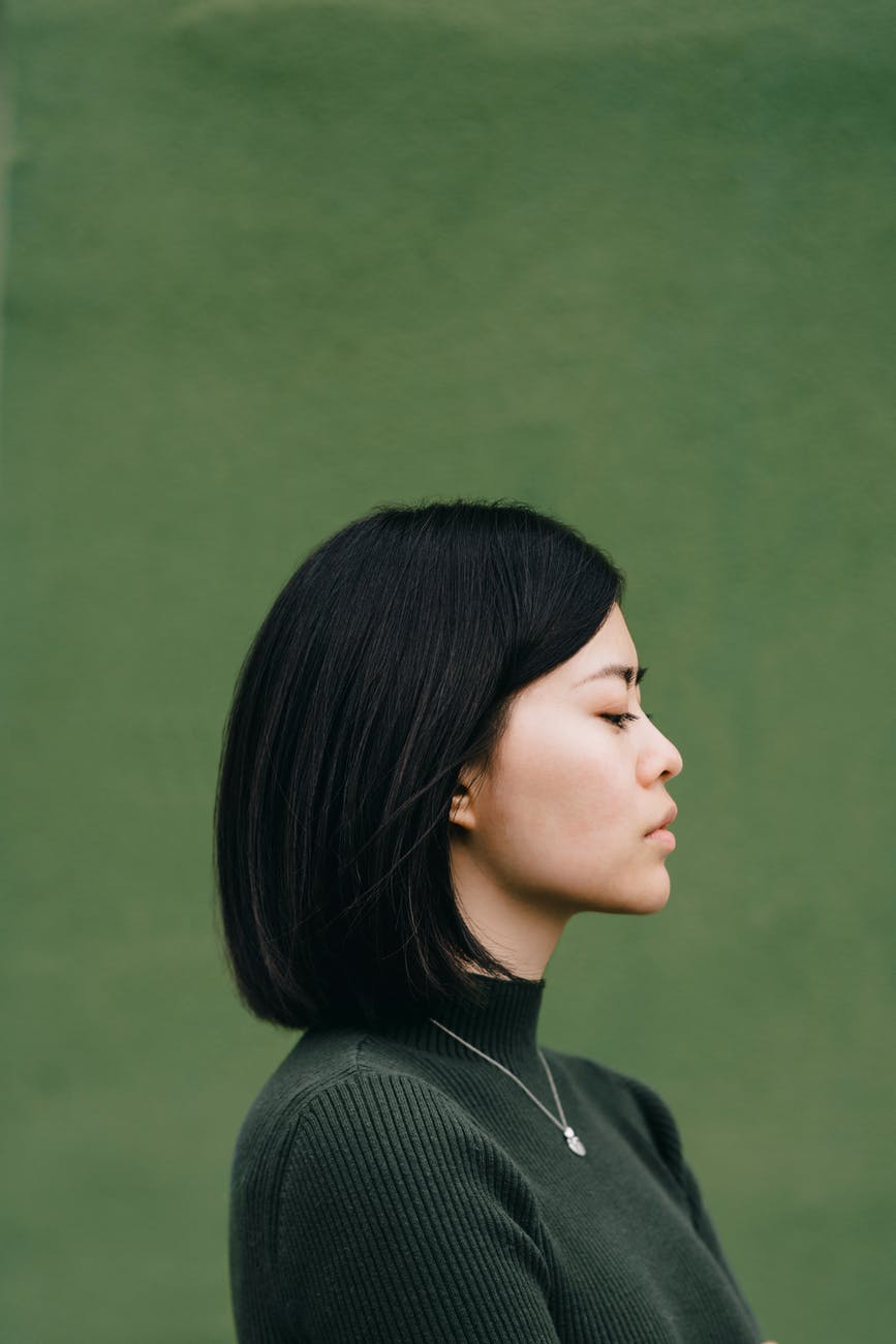 confident asian woman against green background