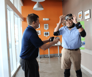 """Alvaro Cabal, a Ford Motors Co. rep, right, and Giancarlos Tapanes, a 17-year-old student from Florida during a """"drunk simulator suit"""" demonstration in Wynwood, Florida. (Daysi Calavia-Robertson/ Press Pass Latino)"""