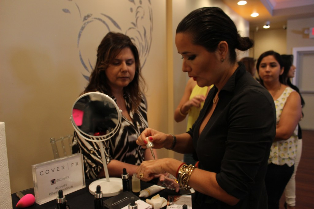 A woman applies make up on another woman at a beauty event.