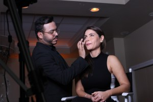 Seasoned make-up artist Roberto Ramos gently dabs some Cover FX Mattifying Primer on host Chiquinquira Delgado. (Daysi Calavia-Robertson/ Press Pass Latino).