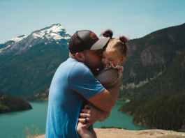man wearing blue crew neck t shirt holding girl near mountains