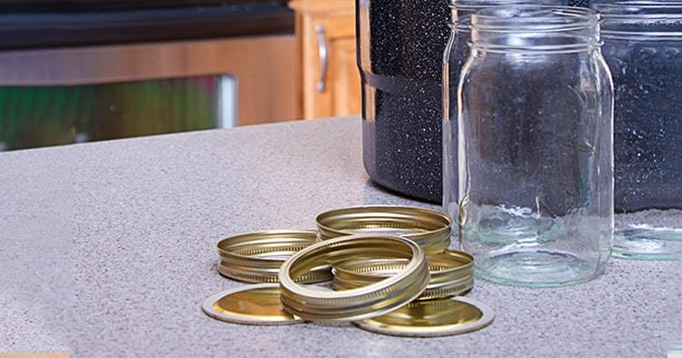 Canning jars with lids, canner or pot in a kitchen setting