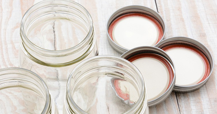 Closeup of three glass canning jars on a rustic wood farmhouse style kitchen table