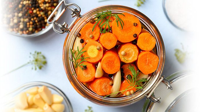 omemade fermented carrots with garlic, dill and pepper in a glass jar. Light blue background. Top view, close-up.