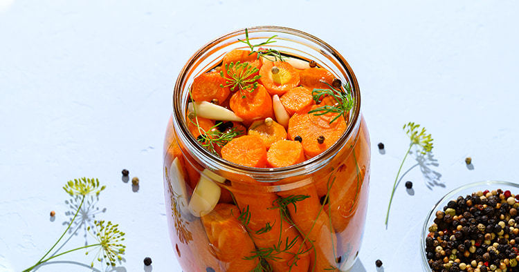 Homemade fermented carrots with garlic, dill and pepper in a glass jar.